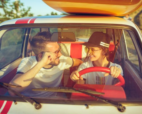 Laughing romantic couple sitting in the car while out on a road trip. Couple having picnic at summer day